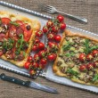 Two square pizzas with fresh arugula and cherry-tomatoes on silv — Стоковое фото #60284559