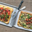 Two square pizzas with fresh arugula and cherry-tomatoes on silv — Foto Stock #60284657