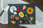 Cheese and fruit set on a dark stone board — Stock Photo
