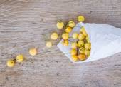 Yellow sweet-cherries in a paperbag on a rought wood surface — Stock Photo