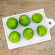 Fresh green figs on a white ceramic board over a black backgroun — Stock Photo #68759429