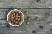 A bawl of gooseberries on a wooden surface — Stock Photo