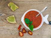 A bawl of tomato soup on a wooden desk — Stock Photo