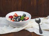 A bawl of oat porridge with fresh berries, honey, almond petals  — Stock Photo