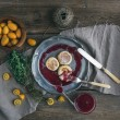 Rustic breakfast set. Russian cheese cakes on a vintage metal plate with lingonberry jam, fresh kumquats, thyme, decoration rope and old dinnerware over rough wooden desk — Stock Photo #68762615