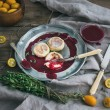 Rustic breakfast set. Russian cheese cakes on a vintage metal plate with lingonberry jam, fresh kumquats, thyme, decoration rope and old dinnerware over rough wooden desk — Stock Photo #68762621