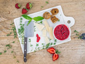 Cheese and fruit set on a white ceramic cutting board — Stock Photo