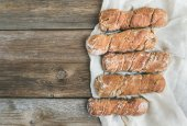 Freshly baked rustic  village bread (baguettes) set on rough woo — Foto Stock