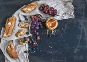 French baguette cut into pieces, red grapes, blueberry and salt caramel sauce on rustic dark background — Stock Photo