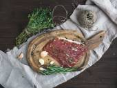 Cured pork meat or prosciutto on a rustic woodem board with garli — Stock Photo