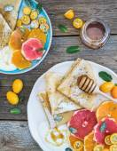 Spring vitamin breakfast set. Thin crepes or pancakes with fresh grapefruit, orange, kumquat, honey, cream and mint leaves over a rustic wood background — Stock Photo