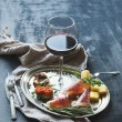 Wine appetizer set. Glass of red wine, vintage dinnerware, brushetta with cherry, dried tomatoes, arugula, parmesan, smoked meat on silver tray over rustic grunge surface — Stock Photo #70114397