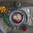 Rustic breakfast set. Russian cheese cakes on a vintage metal plate with lingonberry jam, fresh kumquats, thyme, decoration rope and old dinnerware over rough wooden desk — Stock Photo #70114541