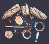 Rustic breakfast set of french baguette broken into pieces, grapefruit, sunflower seeds, almonds and coffee on dark — ストック写真