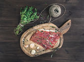 Cured pork meat (prosciutto) on a rustic woodem board with garlic, spices and thyme — Stock Photo