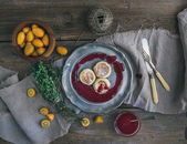 Rustic breakfast set. Russian cheese cakes on a vintage metal plate with lingonberry jam, fresh kumquats, thyme, decoration rope and old dinnerware over rough wooden desk — Stock Photo