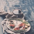 Wine appetizer set. Glass of red wine, vintage dinnerware, brushetta with cherry, dried tomatoes, arugula, parmesan, smoked meat on silver tray over rustic grunge surface — Stock Photo #70219221