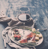 Wine appetizer set. Glass of red wine, vintage dinnerware, brushetta with cherry, dried tomatoes, arugula, parmesan, smoked meat on silver tray over rustic grunge surface — Stock Photo