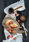Breakfast set. Freshly baked croissants with strawberries, mascarpone, honey and coffee on rustic wooden board over dark grunge backdrop — Stock Photo