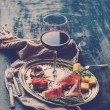 Wine appetizer set. Glass of red wine, vintage dinnerware, brushetta with cherry, dried tomatoes, arugula, parmesan, smoked meat on silver tray over rustic grunge surface — Stock Photo #72788575