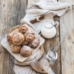 Cinnamon buns with sugar powder on rustic wooden board, jug of milk,  dark grunge surface — Stock Photo #72791203