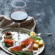 Wine appetizer set. Glass of red wine, vintage dinnerware, brushetta with cherry, dried tomatoes, arugula, parmesan, smoked meat on silver tray over rustic grunge surface — Stock Photo #74015877