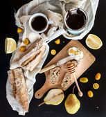 Breakfast set: pot or cezve of coffee, cup on kitchen towel, kumquats, pears, grapefruit, baguette slices with butter cream and honeyl, rustic wooden board over  black backdrop — Stock Photo