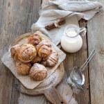 Cinnamon buns with sugar powder on rustic wooden board, jug of milk,  dark grunge surface — Stock Photo #75852429