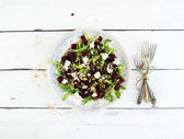 Beetroot salad with arugula, feta cheese, red salt and pumpkin seeds in vintage plate over white rustic wooden background, top view — Stock Photo
