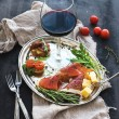 Wine appetizer set. Glass of red wine, vintage dinnerware, brushetta with cherry, dried tomatoes, arugula, parmesan, smoked meat on silver tray over rustic grunge surface — Stock Photo #79071248
