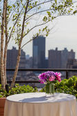 Floral arangement with Roses, Hydrangea and Orchids on city background — Stock Photo