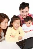 Japanese family of four on laptop computer — Stock Photo