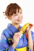 Young woman wearing Japanese kimono with grilled corn — Stockfoto