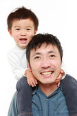 Japanese father giving his son piggy back — Stock Photo