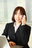 Young Japanese business woman talks with a smart phone — Stock fotografie