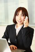 Young Japanese business woman talks with a smart phone — Стоковое фото