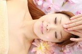 Young Japanese woman getting a face massage — Stock Photo