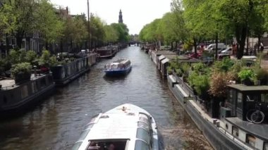 Canal cruise ships in Amsterdam passing by each other with living boats on the side of the canal — Vídeo Stock