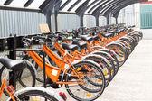 Group of orange bikes still in storage — Stock Photo