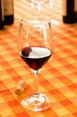 Glass of red wine in the rustic tablecloth — Stock Photo