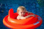 Baby swimming in the orange float — Stock Photo