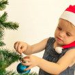 Little girl decorating the christmas tree — Stock Photo #58763845
