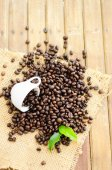Coffee beans with white cup and green leaves — Stock Photo