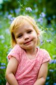 Cute little girl sitting in front of blue flowers field — Stock Photo