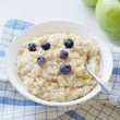Oatmeal porridge in white bowl topped with berries — Stock Photo #70051989