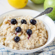 Oatmeal porridge in white bowl topped with berries — Stock Photo #70051993
