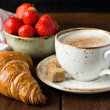 Croissant, strawberries and cup of coffee — Stock Photo #74384255