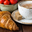 Croissant, strawberries and cup of coffee — Stock Photo #74384257