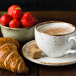 Croissant, strawberries and cup of coffee — Stock Photo #74384253