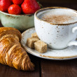 Croissant, strawberries and cup of coffee — Stock Photo #74384267